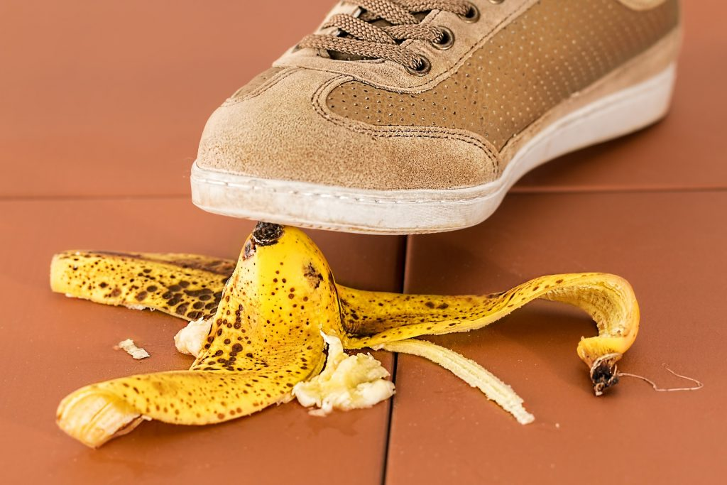 Un pied qui va marcher sur une peau de banane sur le sol